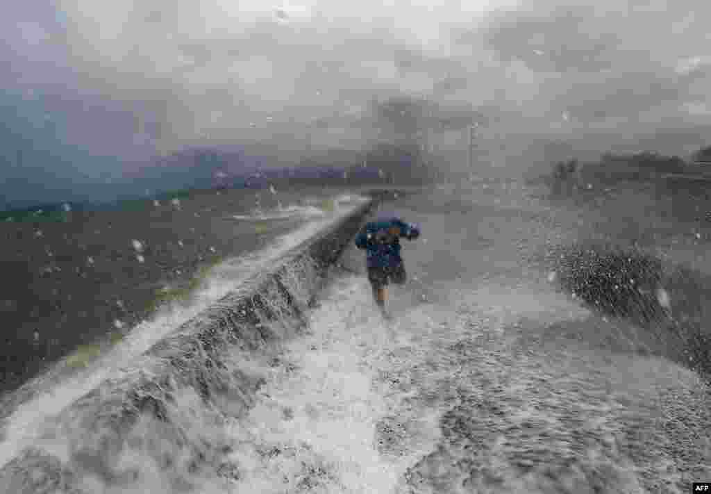 A resident walks past big waves spilling over a wall onto a coastal road in the city of Legaspi in Albay province, south of Manila, as typhoon Melor approaches the city. More than 700,000 people fled the central Philippines amid threats of giant waves, floods and landslides as the powerful typhoon approached the archipelago nation, officials said.