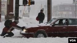 Seorang warga berusaha membantu pengendara mobil yang terjebak salju di kota St. Paul, Minnesota.