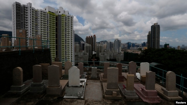 Headstones stand at a cemetery facing residential apartments in downtown Hong Kong, May 29, 2014