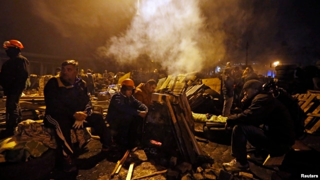 Anti-government protesters rest next to a barricade in Independence Square in Kyiv, Ukraine, Feb. 21, 2014.