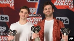"""Drew Taggart, left, and Alex Pall, of the Chainsmokers, pose with the awards for best new artist, best new pop artist and dance song of the year for """"Closer"""" in the press room at the iHeartRadio Music Awards at the Forum on March 5, 2017."""
