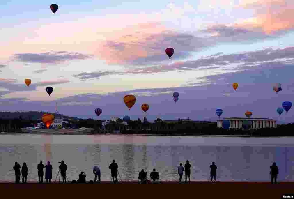 មនុស្សម្នាមើលប៉ោងៗហោះនៅពីលើរដ្ឋធានីរបស់អូស្រា្តលី ក្នុងពិធីបុណ្យ Canberra Balloon។
