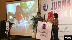 Baiq Nuril menerima penghargaan Tasrif Award dari perwakilan Dewan Juri, Devi Asmarani dari Magdalene dan Lexy Rambadeta dari Jakartanicus. (VOA/Rio Tuasikal)