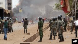 FILE - Guinea security forces, center, face people rioting and burning rubbish and other goods in the streets of Conakry, April 13, 2015.