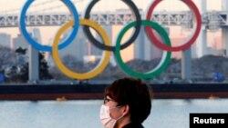 Seorang pria mengenakan masker di tengah wabah COVID-19 di depan cincin Olimpiade raksasa di Tokyo, Jepang, 13 Januari 2021. (Foto: REUTERS/Kim Kyung-Hoon)