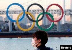 Seorang pria mengenakan masker di tengah pandemi COVID-19 di depan arena Cincin Olimpiade raksasa di Tokyo, Jepang, 13 Januari 2021. (REUTERS / Kim Kyung-Hoon)