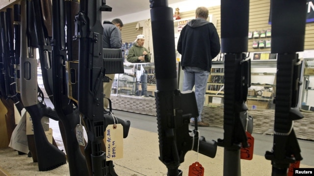 File - Customers shop for handguns through a rack of assault rifles at the Guns-R-Us gun shop in Phoenix, Arizona.