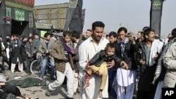 一名男子抱著一名星期二在喀布爾的一次爆炸中受傷的男童
