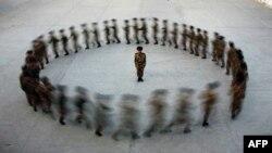 Một chỉ huy đứng nhìn các cảnh sát mới được tuyển dụng tập luyện ở Tân Cương. Tân Cương đã chứng kiến một sự tăng vọt trong các vụ bạo động năm ngoái.
