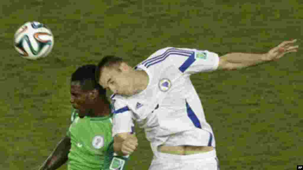Nigeria's Emmanuel Emenike, left, and Bosnia's Toni Sunjic go for a header.