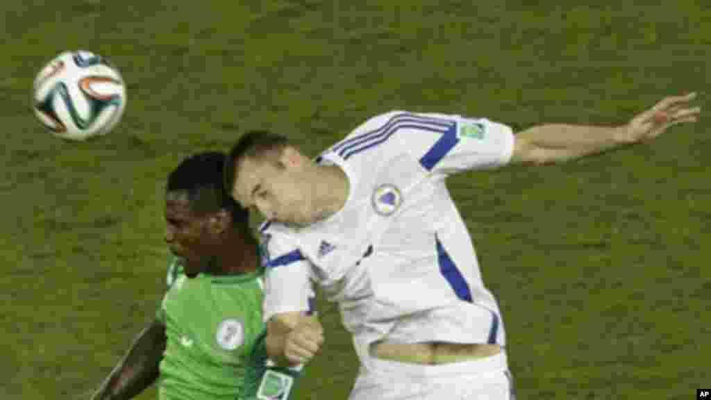 Nigeria's Emmanuel Emenike, left, and Bosnia's Toni Sunjic go for a header.