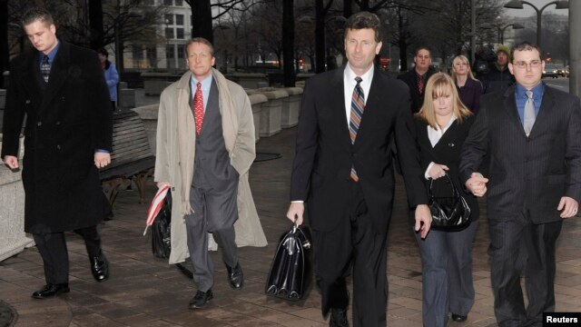 FILE - Two Blackwater guards (L & R) leave the federal courthouse in Washington with their legal team and supporters after being arraigned in a 2007 shooting in Baghdad, January 6, 2009.