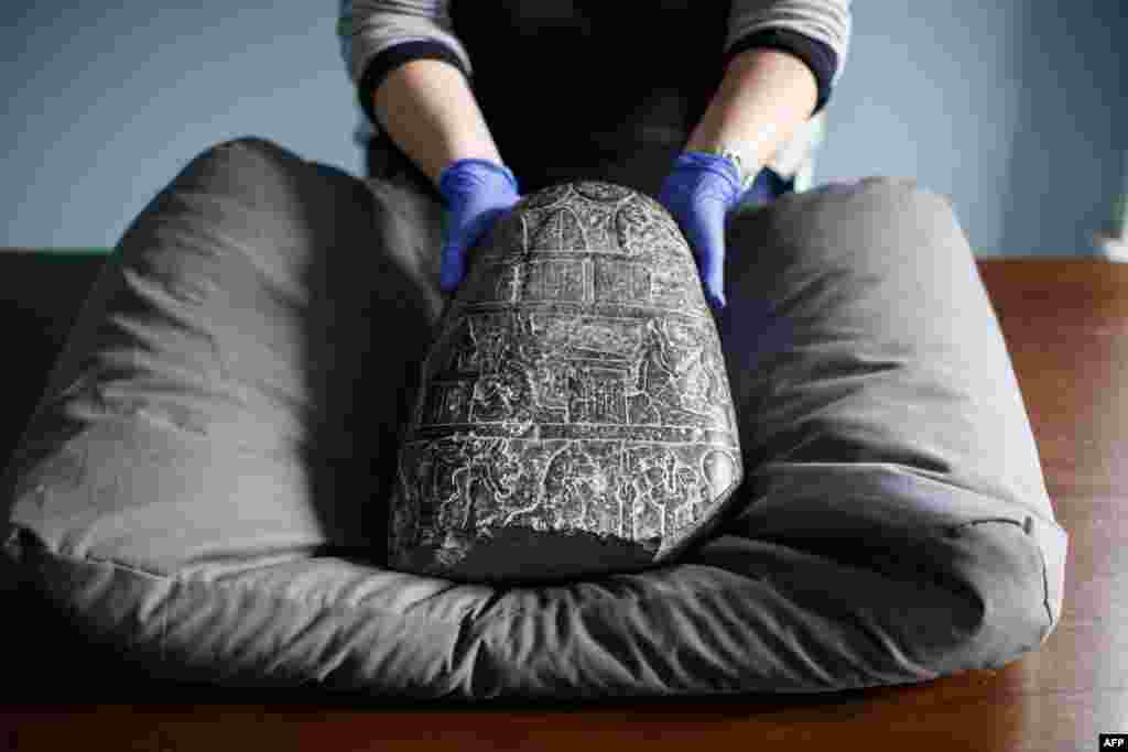 A gallery assistant poses with a Babylonian cuneiform kudurru (boundary stone) which was looted from Iraq at the British museum in London. The kudurru, seized at London's Heathrow airport in 2012, was handed over to representatives of the Iraq embassy at the British museum.
