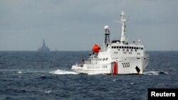 资料照:一艘中国海警船在南中国海上的一座中国海上钻井平台旁驶过。(2014年6月13日)