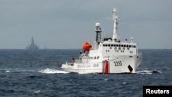 一艘中國海警船在南中國海上的一座中國海上鑽井平台旁駛過。(2014年6月13日)