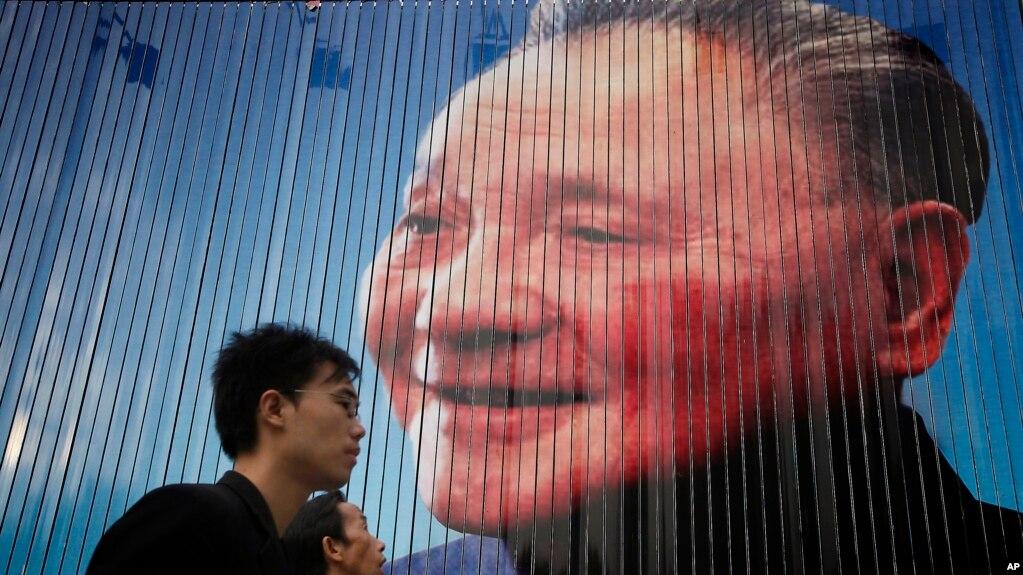 Một người đi ngang qua tấm áp phích có ảnh Đặng Tiểu Bình, một lãnh đạo của Đảng Cộng sản Trung Quốc trước đây. Các chuyên gia cho rằng sự phát triển kinh tế của Trung Quốc bị chậm lại là do vấn đề trong nước hơn là do thương chiến với Mỹ.