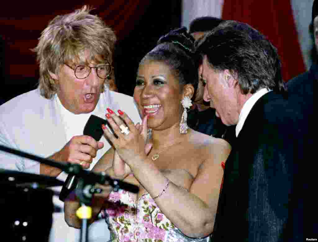 Rock star Rod Stewart (L) and actor Dustin Hoffman (R) join music legend Aretha Franklin on stage for a song during a show being taped in New York April 27, 1993.