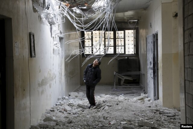 FILE - A boy inspects damage inside his school, due to what activists said was an airstrike carried out the previous day by the Russian air force in Injara town, Aleppo countryside, Syria, Jan. 12, 2016.