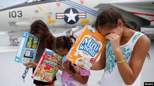Michelle Campano (Right) and her sisters Jennifer (Middle) and Lauren Campano, all of Rockville, Maryland, check on the position of the sun using homemade solar viewers from the flight deck of the Naval museum ship U.S.S. Yorktown during the Great America