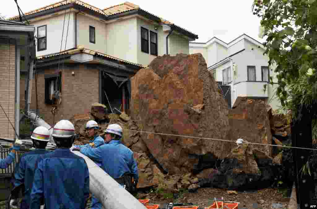 "A house and an electric pole smashed by large rocks from a collapsed slope caused by heavy rain in Kamakura, suburban Tokyo. At least 17 people died as Typhoon Wipha, the ""strongest in 10 years"", passed close to Tokyo, causing landslides that swallowed houses."