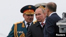 Russian President Vladimir Putin (C) and Defence Minister Sergei Shoigu (L) review the Russian fleet in Sevastopol May 9, 2014.