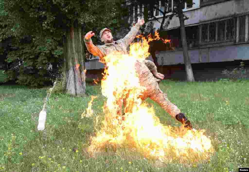 An officer on duty attempts to knock down the flame as Ukrainian former serviceman Serhii Ulianov sets himself on fire while protesting against his dismissal from the Armed Forces in front of the Ukrainian Defense Ministry headquarters in Kiev, Ukraine.