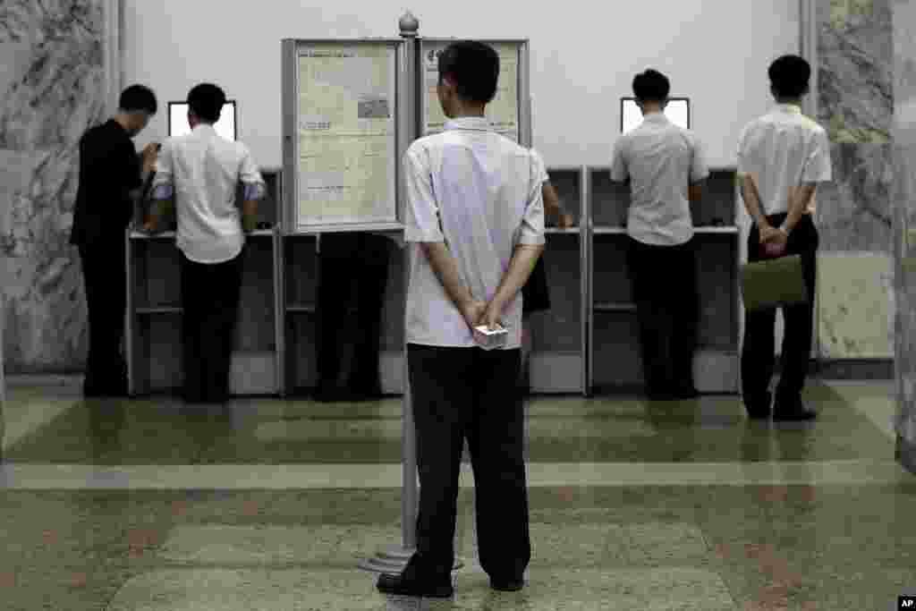 평양 주민들이 인민대학당 컴퓨터실에서 인트라넷을 이용하는 가운데, 한 남성이 게시판 신문을 읽고 있다.