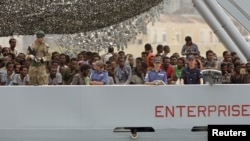 Migrants arrive on the British vessel HMS Enterprise before disembarking in the Sicilian harbour of Catania, Italy, Oct. 6, 2015.