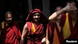 FILE - Tibetan monks walk in an alley at Majnu Ka Tila, a Tibetan refugee camp in New Delhi, India, April 27, 2016.