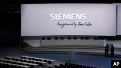 FILE - Security stewards of German industrial conglomerate Siemens wait for the start of the annual shareholders meeting in Munich, Germany, Feb. 1, 2017.