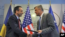 US Assistant Secretary of State Philip Gordon (L) shakes hand with Kosovo Prime Minister Hashim Thaci after signing an agreement to support education authorities in capital Pristina, June 16, 2011