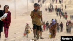 FILE - Children from the minority Yazidi sect, fleeing violence from Islamic State militants in Sinjar, Iraq, make their way toward the town of Elierbeh of Al-Hasakah Governorate, near the Syrian border, Aug. 10, 2014.