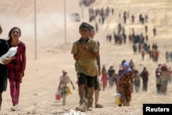 FILE - Children from the minority Yazidi sect, fleeing violence from Islamic State militants Sinjar, Iraq, make their way toward the Syrian border town of Elierbeh, Aug. 10, 2014.