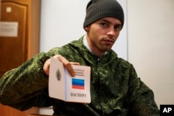 FILE - A Russia-backed rebel shows a passport issued by the self-proclaimed Luhansk Peoples Republic, in Luhansk, eastern Ukraine, Oct. 27, 2015.