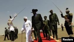 Rais wa Sudan Omar al-Bashir (L)mwenye kilemba cheupe na Rais wa Sudan Kusini, Salva Kiir(R) kwenye uwanja wa ndege wa Khartoum