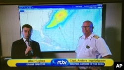 A Saturday, Feb. 27, 2016 photo provided by John Turell shows the television screen in a stateroom aboard the Anthem of the Seas cruise ship, where cruise director Abe Hughes and Captain Anders Ingobrigtsen explain to passengers that the cruise was being cut two days short because of a storm developing off Cape Hatteras.