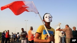Bahraini anti-government protesters, including a masked boy carrying a national flag, gather for a march in A'ali, Bahrain, April 12, 2013.