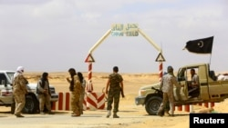 FILE - Militants have been targeting Libyan oil fields and foreign workers. In this March 2014 photo, fighters under Libyan rebel leader Ibrahim Jathran guard the entrance to al-Ghani oil field, which they controlled at the time.