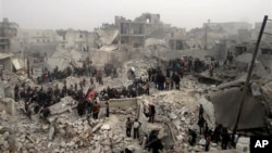 This citizen journalism image from the Aleppo Media Center (AMC) shows people searching debris of destroyed buildings after Syrian government forces airstrike, Jabal Bedro, Aleppo, Feb. 19, 2013.