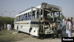 Security officials survey a damaged bus which was hit by a bomb attack in Quetta, Pakistan, June 18, 2012.