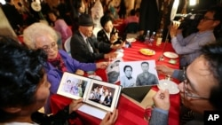 Family members from South Korea and North Korea show their family photos each others during the Separated Family Reunion Meeting at the Diamond Mountain resort in North Korea, Oct. 24, 2015.
