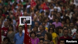 """Seorang pengunjuk rasa membawa photo PM Spanyol Mariano Rajoy, yang menggambarkannya sebagai tokoh cerita kartun Pinokio saat mengatakan """"Saya tidak berbohong"""" dalam aksi protes menentang langkah penghematan di Madrid (20/6)."""