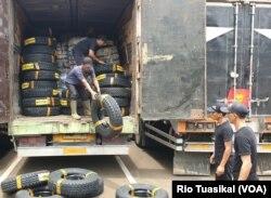 Petugas menurunkan ban yang berhasil disita bea cukai bersama bal pakaian dan karpet, Bandung, 11 Maret 2020. (Foto: Rio Tuasikal)