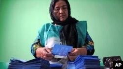 Petugas komisi pemilihan umum Afghanistan menghitung kertas suara di sebuah TPS di Mazar-i-Sharif (14/6). (AP/Mustafa Najafizada)