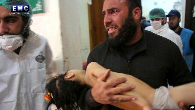 Esta foto del 4 de abril de 2017, proporcionada por el grupo activista contra el gobierno sirio Edlib Media Center, muestra a un hombre llevando un niño después de un ataque químico.