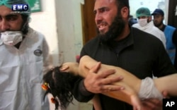 FILE - This April 4, 2017, photo provided by the Syrian anti-government activist group Edlib Media Center shows a man carrying a child following a suspected chemical attack at a makeshift hospital in the town of Khan Sheikhoun, Idlib province, Syria. Walid Moallem, Syria's foreign minister, told reporters April 6 that his country didn't use chemical weapons in the attack.