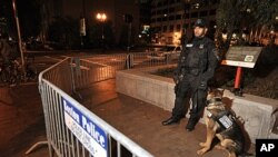 A police officer and dog guard stand behind barricades after police arrested people sleeping in an expansion of the Occupy Boston tent village on the Rose Kennedy Greenway in Boston, in the early morning hours, October 11, 2011.
