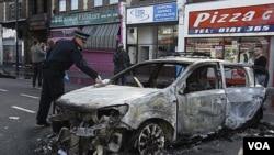 Seorang polisi memeriksa sebuah mobil dinas kepolisian yang hangus terbakar akibat kerusuhan di Tottenham, Minggu (7/8).