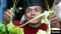 Seorang pedagang kaki lima Indonesia menjual ketupat, di Jakarta 24 November 2003, menjelang Idul Fitri. (Foto: Reuters)