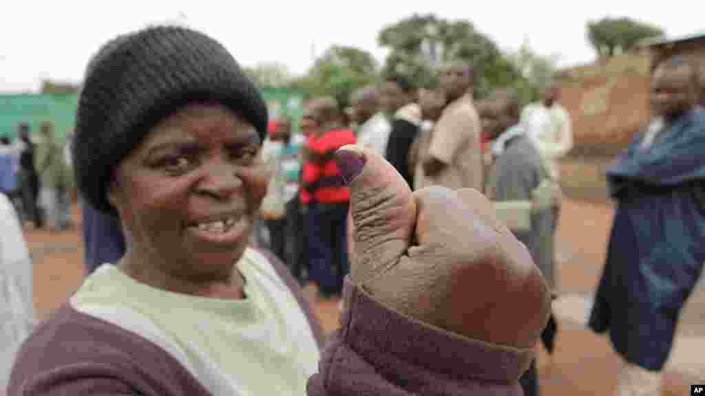 Une femme montre son pouce taché d'encre après avoir placéson vote dans l'urne le jour de l'élection présidentielle à Lusaka, 20 janvier 2015.